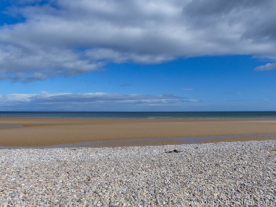 shingle, beach, tidal sands and a blue sky with a few clouds above the water