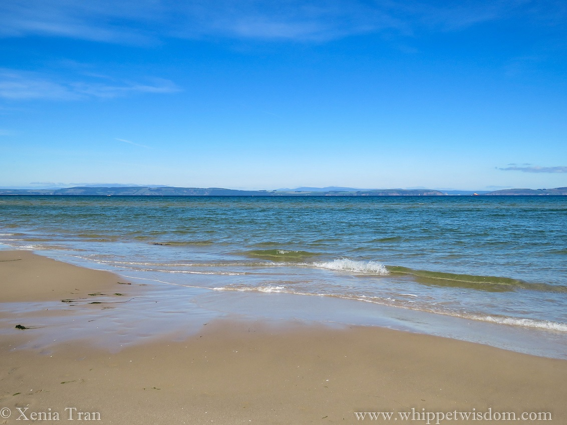 clear blue sky above hazy blue mountains and a calm green blue sea