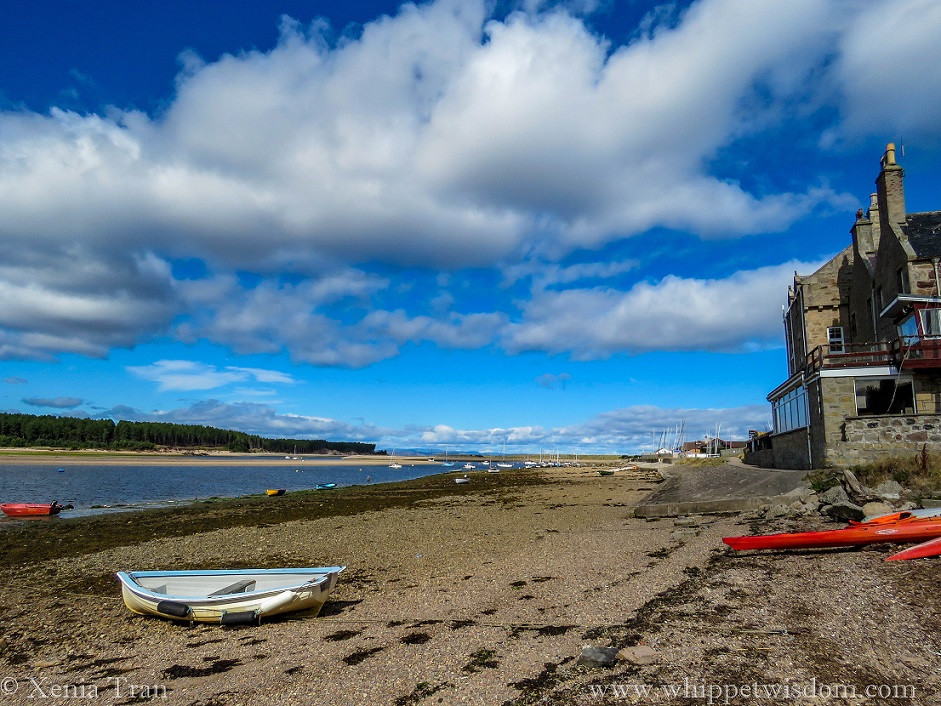 Findhorn Bay at low tide with canoes and rowing boats resting on shingle