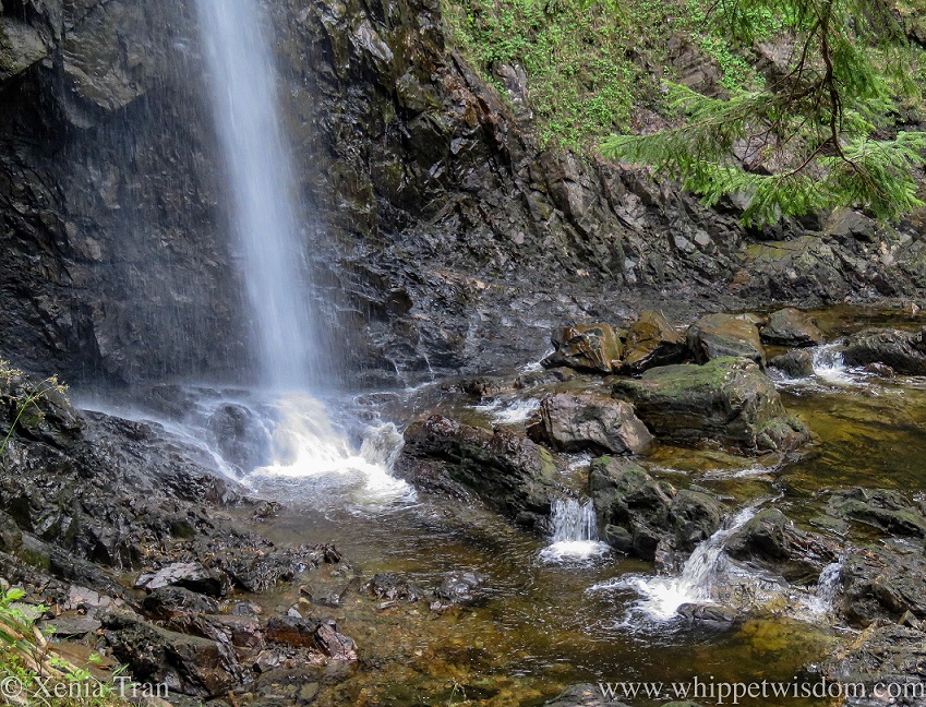 the lower part of a water fall splashing into a burn with smaller cascades around it