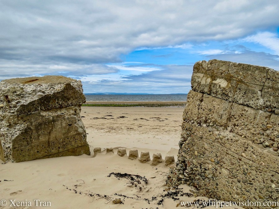 two crumbling WW2 defences with a sandcastle between them on the beach