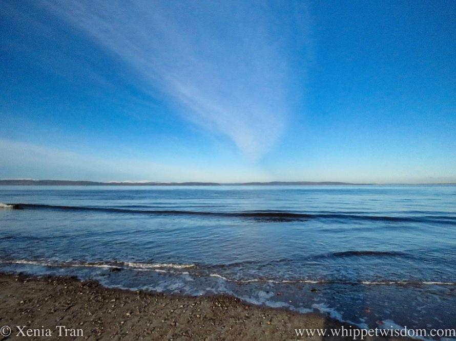 a funnel cloud spreading above a glacier-blue sea